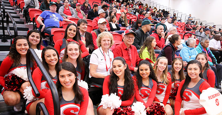 The Bizzinis at a basketball game with the cheer team