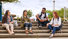 group of diverse students sitting together on campus stairs