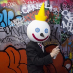 a person dressed in a suit and wearing a Jack in the Box fast food company mask holds a spray can against a wall with grafitti