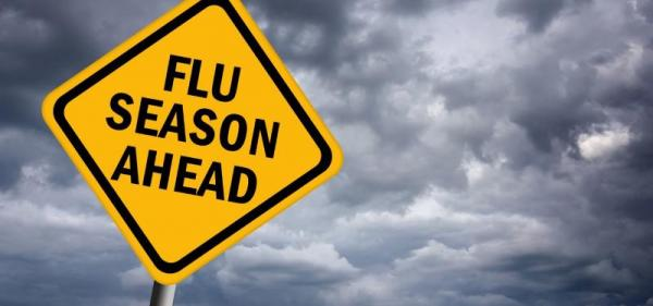 Sign stating Flu Season Ahead with a cloudy background.