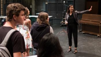 Cynthia DeCure directs drama students during rehearsal of a play.